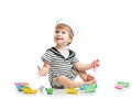 Baby sailor playing with paper boats cute boy hat Stock Photo
