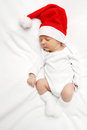 Baby with santa claus hat sleeping on bed Royalty Free Stock Image