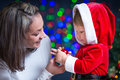 Baby Santa Claus and mother over bright festive Stock Photo