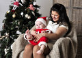 Baby in santa costume with mother sit on chair near christmas tree together Stock Photo