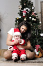 Baby in santa costume sit with mother on decorating christmas tree Stock Photo