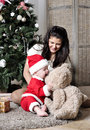Baby in santa costume sit with mother on decorating christmas tree Royalty Free Stock Photo