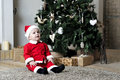 Baby in santa costume sit near decorating christmas tree child and look Stock Photo