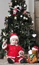 Baby in santa costume sit near decorating christmas tree with toy dog Stock Photography