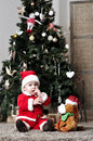 Baby in santa costume sit near decorating christmas tree with toy dog Royalty Free Stock Photo