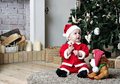 Baby in santa costume sit near decorating christmas tree with toy dog Royalty Free Stock Photography