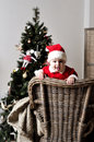 Baby in santa costume stand on chair near christmas tree Stock Images