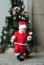 Baby in santa costume standing on decorating christmas tree near Royalty Free Stock Images