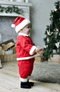 Baby in santa costume standing on decorating christmas tree near Stock Photo