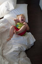 Baby screaming on bed clothes floor Royalty Free Stock Photo