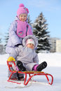 Baby sits on sled and little sister stands behind him dressed in warm clothes red at winter Royalty Free Stock Images