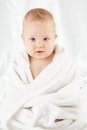 Baby sits wrapped in bath towel after bathing Stock Photo