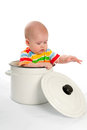 Baby sitting in the big saucepan. Royalty Free Stock Image