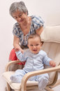 Baby sitting on chair and laughing with grandmother Royalty Free Stock Images