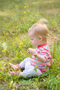 Baby sitting on the grass in the field. Royalty Free Stock Photography