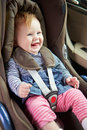 Baby sitting happily in car seat smiling away from camera Stock Photography