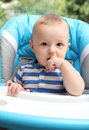 Baby sitting in highchair boy Stock Photo