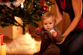Baby sitting near Christmas tree with toy Stock Photography