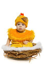 Baby sitting in nest in chicken costume Royalty Free Stock Photo