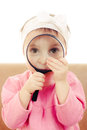 Baby sitting at a table looking through magnifying glass Stock Images