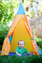Baby sitting in a tepee Stock Photos