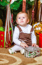 Baby sitting under christmas tree in room Royalty Free Stock Photography