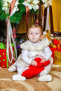 Baby sitting under christmas tree in room Stock Image