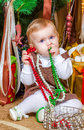 Baby sitting under christmas tree in room girl Stock Images