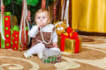 Baby sitting under christmas tree in room girl Stock Photography