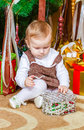 Baby sitting under christmas tree in room girl Stock Photos