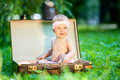Baby sitting in vintage suitcase in garden Royalty Free Stock Photos