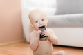 Baby sitting on wooden floor and playing with a mobile phone Royalty Free Stock Photos