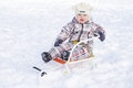 Baby on sledge in winter age of year sitting Stock Image