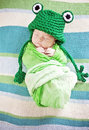 Baby sleeping newborn while wrapped in green blanket wearing frog hat Royalty Free Stock Images