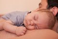 Baby sleeps on dad tender care of his father Stock Image
