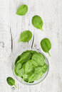 Baby spinach leaves in bowl on white rustic table, organic and healthy food Royalty Free Stock Photo