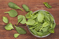 Baby spinach leaves spilling glass bowl onto red barn wood table Stock Photo