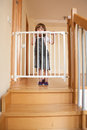 Baby and the stair gate small approaching safety of stairs Stock Photos