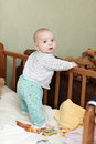 Baby standing in cot Stock Photography