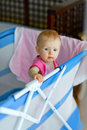 Baby standing in playpen Stock Image