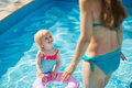 Baby standing in pool and looking on mother Royalty Free Stock Photo