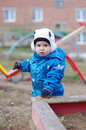 Baby standing by sandpit on playground age of year Stock Photo