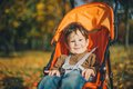 Baby in a stroller in autumn park happy Royalty Free Stock Photos