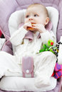 Baby in a stroller bites a bagel laying down Royalty Free Stock Images