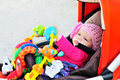 Baby in stroller with toys playing Stock Photo