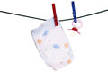 Baby stuff diaper and pacifier on a clothesline Royalty Free Stock Images