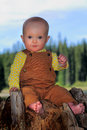 Baby on stump a closeup of cute barefooted wearing overalls sitting a in the forest shallow depth of field Stock Photo