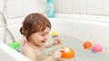 Baby   swimming with toys in bath Royalty Free Stock Photos