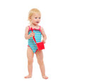 Baby in swimsuit holding bucket and shovel Stock Photo