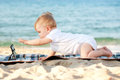Baby with tablet pc on the beach. Royalty Free Stock Photo